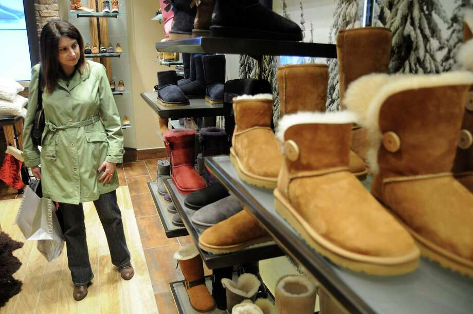 "Elise Neal shops for boots at the Ugg store at the Galleria in Houston. One researcher says ""the Ugg boot has become a holiday tradition rivaling the fruitcake."" Photo: Houston Chronicle Photos"