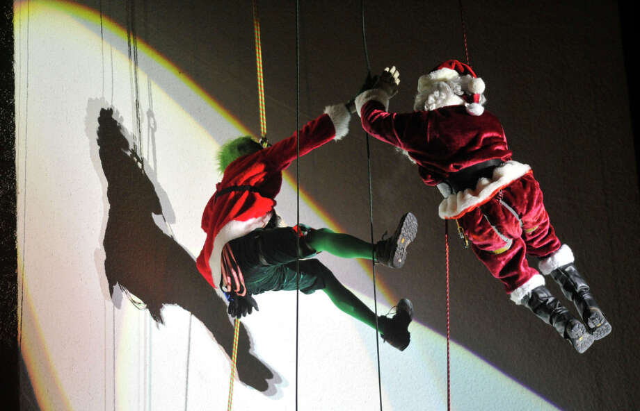The Grinch and Santa, played by Jason Teitelbaum and Brian Van Orsdel respectively, high-five each other while rapeling down the Landmark Tower during the Heights and Lights event in downtown Stamford, Conn., on Sunday, Dec. 8, 2013. Photo: Jason Rearick / Stamford Advocate