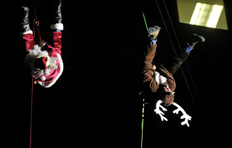 Santa and Rudolph the Red Nose Reindeer, played by Brian Van Orsdel, left, and Ronnie Markey, flip upside-down while rapeling from the Landmark Tower during the Heights and Lights event in downtown Stamford, Conn., on Sunday, Dec. 8, 2013. Photo: Jason Rearick / Stamford Advocate