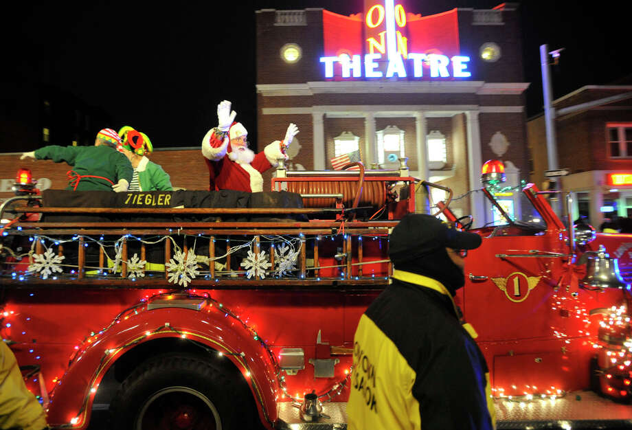 Santa rides a fire truck up Bedford Street before the tree-lighting ceremony at Latham Park during the Heights and Lights event in downtown Stamford, Conn., on Sunday, Dec. 8, 2013. Photo: Jason Rearick / Stamford Advocate