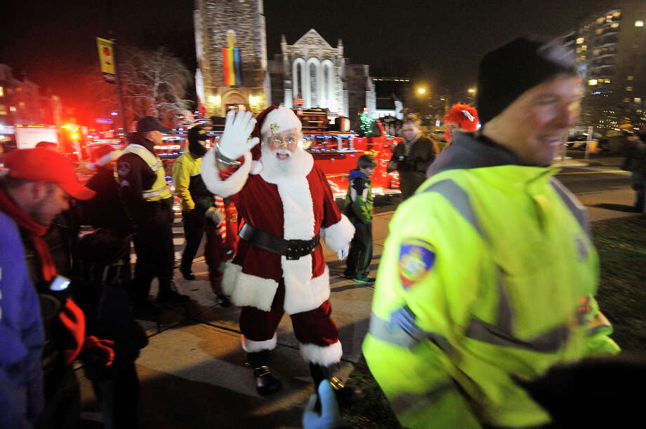 Santa gets a police escort to the stage before the tree-lighting ceremony at Latham Park during the Heights and Lights event in downtown Stamford, Conn., on Sunday, Dec. 8, 2013. Photo: Jason Rearick / Stamford Advocate