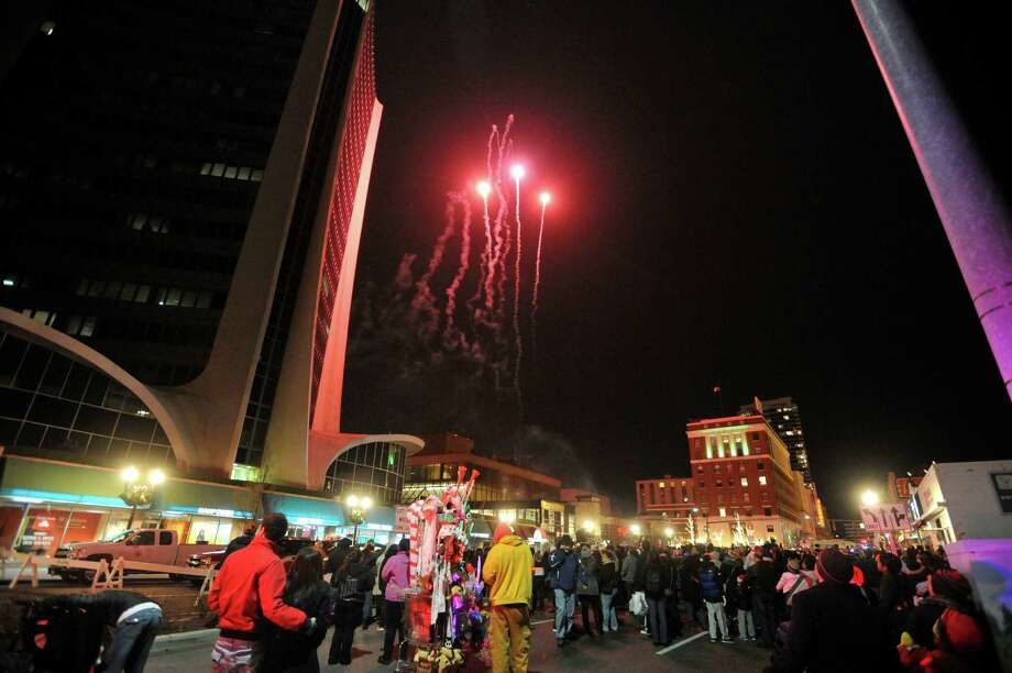 Fireworks go off at the base of the Landmark Tower after Santa and his friends rappeled down the tower during the Heights and Lights event in downtown Stamford, Conn., on Sunday, Dec. 8, 2013. Photo: Jason Rearick / Stamford Advocate