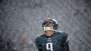 Philadelphia Eagles' Nick Foles warms up as snow falls before an NFL football game against the Detroit Lions, Sunday, Dec. 8, 2013, in Philadelphia. (AP Photo/Matt Rourke)