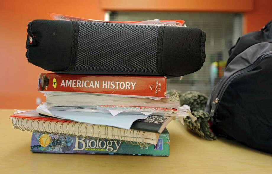 Eighth-grader Ahmeik Robinson's books he carries home in a backpack on his unicycle from Stephen and Harriet Myers Middle School on Wednesday, Dec. 4, 2013 in Albany, N.Y. Robinson rides his unicycle to and from school everyday. (Lori Van Buren / Times Union) Photo: Lori Van Buren / 0024896A