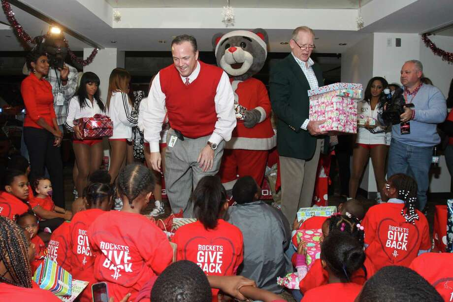 Rockets CEO Tad Brown, center left, and Houston Chronicle Chairman Jack Sweeney hand out gifts to Goodfellows recipients during a party Sunday at a Toyota Center suite. The Rockets donated $50,000 to the program. Photo: Gary Fountain, Freelance / Copyright 2013 Gary Fountain.