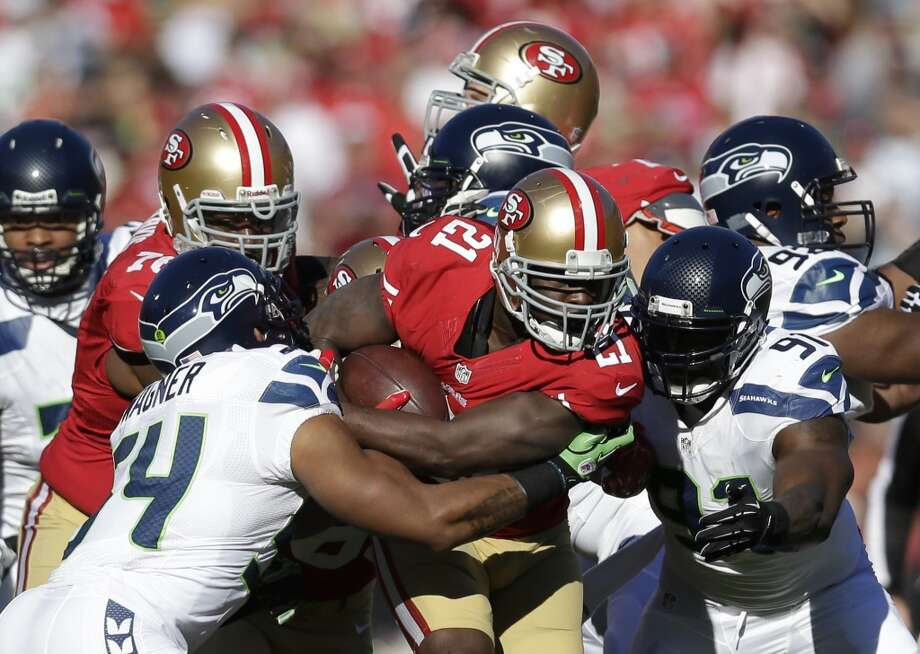 San Francisco 49ers running back Frank Gore carries the ball before being stopped by Seattle Seahawks middle linebacker Bobby Wagner, left, and defensive end Chris Clemons (91) in the first half of an NFL football game, Sunday, Dec. 8, 2013, in San Francisco. (AP Photo/Marcio Jose Sanchez) Photo: Marcio Jose Sanchez, AP