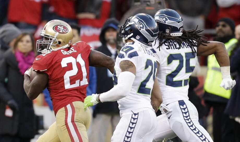 San Francisco 49ers running back Frank Gore, left, carries the ball on a 51-yard run as Seattle Seahawks free safety Earl Thomas (29) and cornerback Richard Sherman (25) look on in the fourth quarter of an NFL football game, Sunday, Dec. 8, 2013, in San Francisco. The 49ers defeated the Seahawks 19-17. (AP Photo/Ben Margot) Photo: Ben Margot, ASSOCIATED PRESS