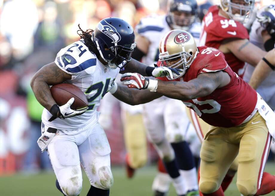 Seattle Seahawks running back Marshawn Lynch, left, carries the ball as San Francisco 49ers outside linebacker Ahmad Brooks, right defends in the second half of an NFL football game, Sunday, Dec. 8, 2013, in San Francisco. (AP Photo/Marcio Jose Sanchez) Photo: Marcio Jose Sanchez, AP