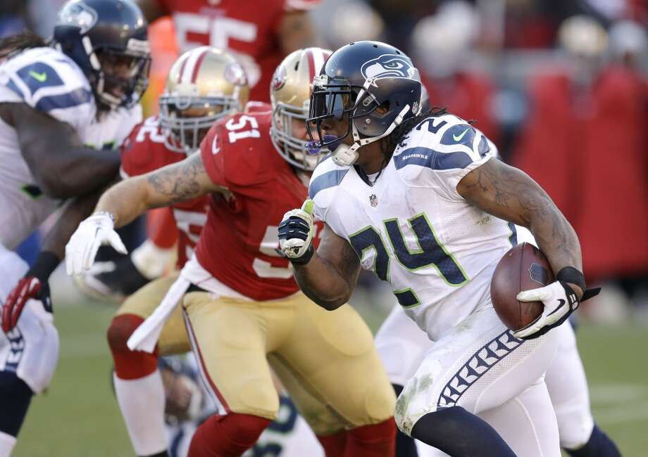 Seattle Seahawks running back Marshawn Lynch, right, carries the ball as San Francisco 49ers outside linebacker Dan Skuta (51) looks on in the second half of an NFL football game, Sunday, Dec. 8, 2013, in San Francisco. (AP Photo/Ben Margot) Photo: Ben Margot, AP