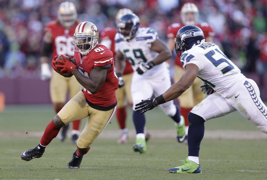 San Francisco 49ers wide receiver Anquan Boldin, left, runs with the ball as Seattle Seahawks middle linebacker Bobby Wagner, right, looks on in the second half of an NFL football game, Sunday, Dec. 8, 2013, in San Francisco. (AP Photo/Marcio Jose Sanchez) Photo: Marcio Jose Sanchez, AP