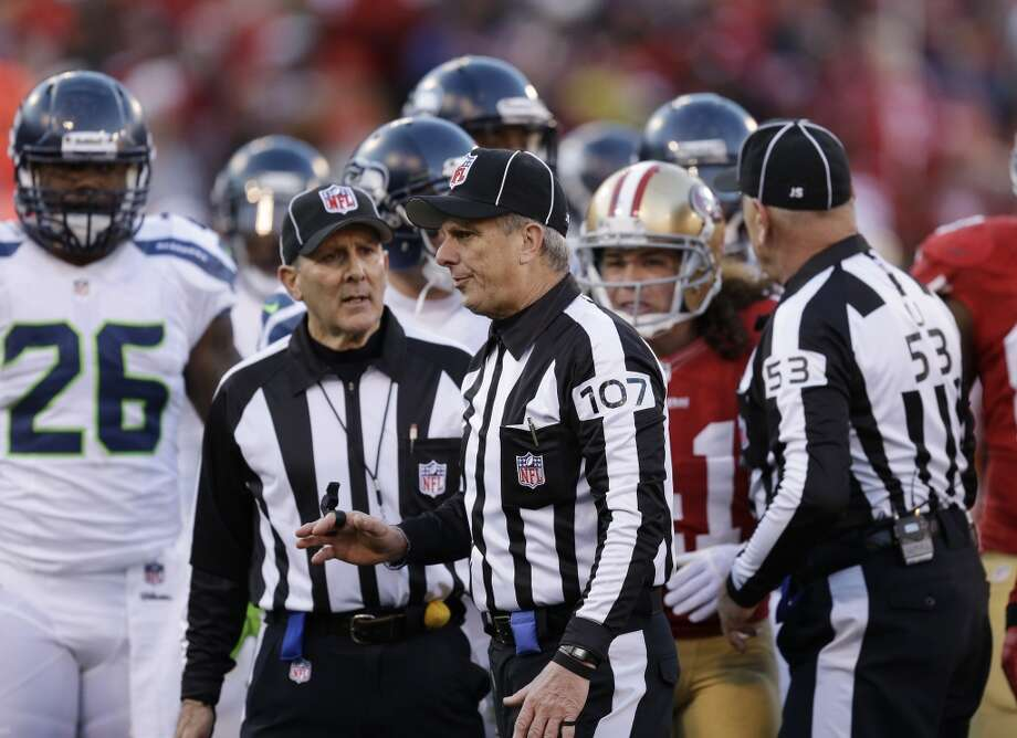 Officials including line judge Ron Marinucci (107) and umpire Garth DeFelice (53) confer  in the second half of an NFL football game between the San Francisco 49ers and the Seattle Seahawks, Sunday, Dec. 8, 2013, in San Francisco. At left is Seattle Seahawks fullback Michael Robinson. (AP Photo/Ben Margot) Photo: Ben Margot, AP