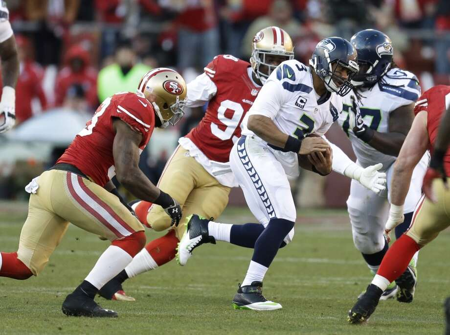 Seattle Seahawks quarterback Russell Wilson (3) keeps the ball as San Francisco 49ers inside linebacker NaVorro Bowman, and outside linebacker Aldon Smith, second from left, close in during the second half of an NFL football game, Sunday, Dec. 8, 2013, in San Francisco. (AP Photo/Ben Margot) Photo: Ben Margot, AP