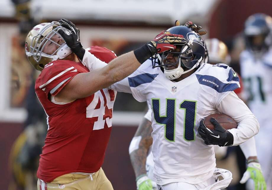 Seattle Seahawks cornerback Byron Maxwell, right, runs with the ball after a pass interception as San Francisco 49ers fullback Bruce Miller, left, tries to make the stop in the second half of an NFL football game, Sunday, Dec. 8, 2013, in San Francisco. (AP Photo/Ben Margot) Photo: Ben Margot, AP