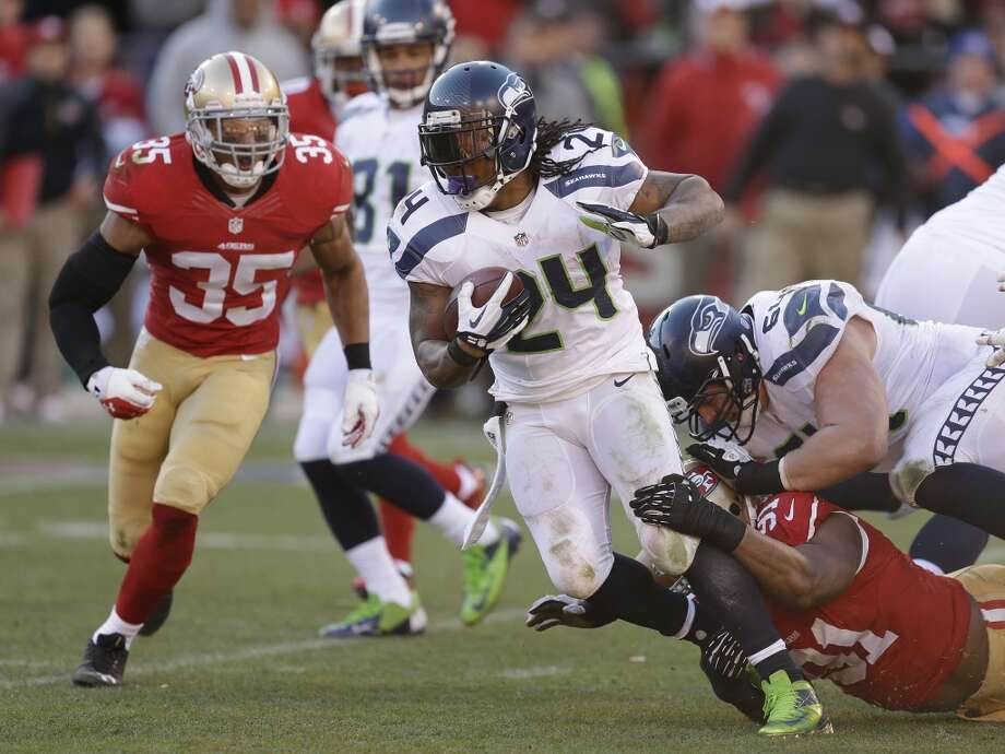 Seattle Seahawks running back Marshawn Lynch carries the ball as San Francisco 49ers defensive end Ray McDonald (91) tries to make the stop in the second half of an NFL football game, Sunday, Dec. 8, 2013, in San Francisco. At left is San Francisco 49ers free safety Eric Reid (35) and at right is Seattle Seahawks guard J.R. Sweezy (64). (AP Photo/Ben Margot) Photo: Ben Margot, AP
