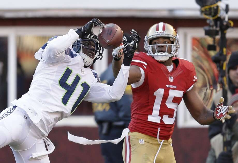 Seattle Seahawks cornerback Byron Maxwell, left, intercepts a pass intended for San Francisco 49ers wide receiver Michael Crabtree, right, in the second half of an NFL football game, Sunday, Dec. 8, 2013, in San Francisco. (AP Photo/Ben Margot) Photo: Ben Margot, ASSOCIATED PRESS