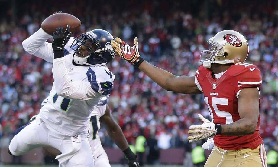 Seattle Seahawks cornerback Byron Maxwell, left, intercepts a pass intended for San Francisco 49ers wide receiver Michael Crabtree, (15), in the second half of an NFL football game, Sunday, Dec. 8, 2013, in San Francisco. (AP Photo/Marcio Jose Sanchez) Photo: Marcio Jose Sanchez, ASSOCIATED PRESS
