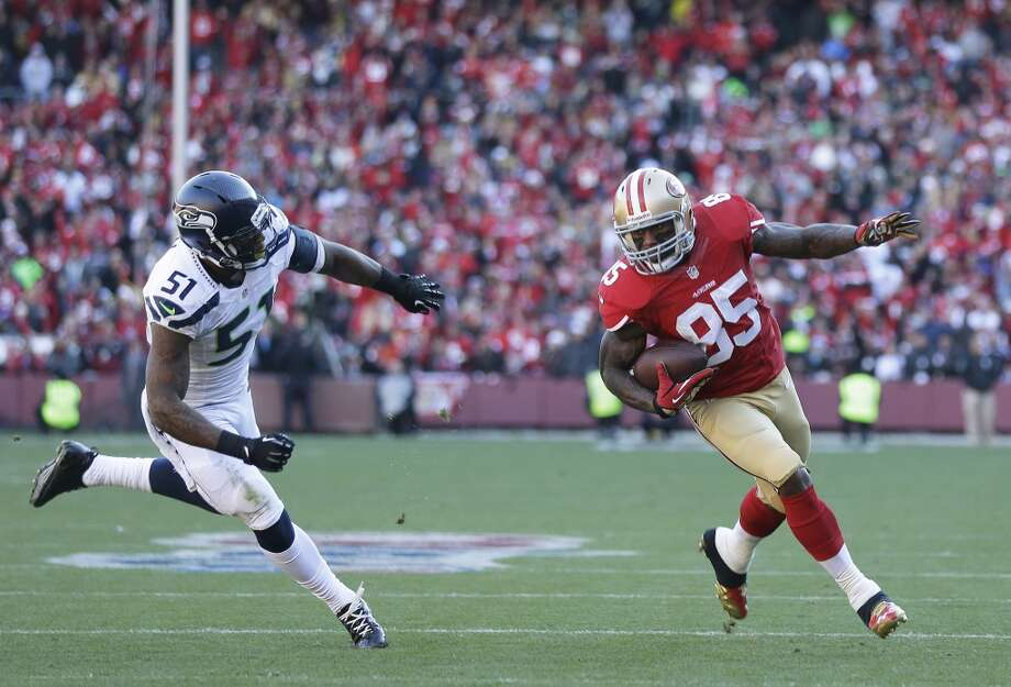 San Francisco 49ers tight end Vernon Davis, right, runs with the ball as Seattle Seahawks outside linebacker Bruce Irvin, left, looks on in the first half of an NFL football game, Sunday, Dec. 8, 2013, in San Francisco. (AP Photo/Marcio Jose Sanchez) Photo: Marcio Jose Sanchez, AP