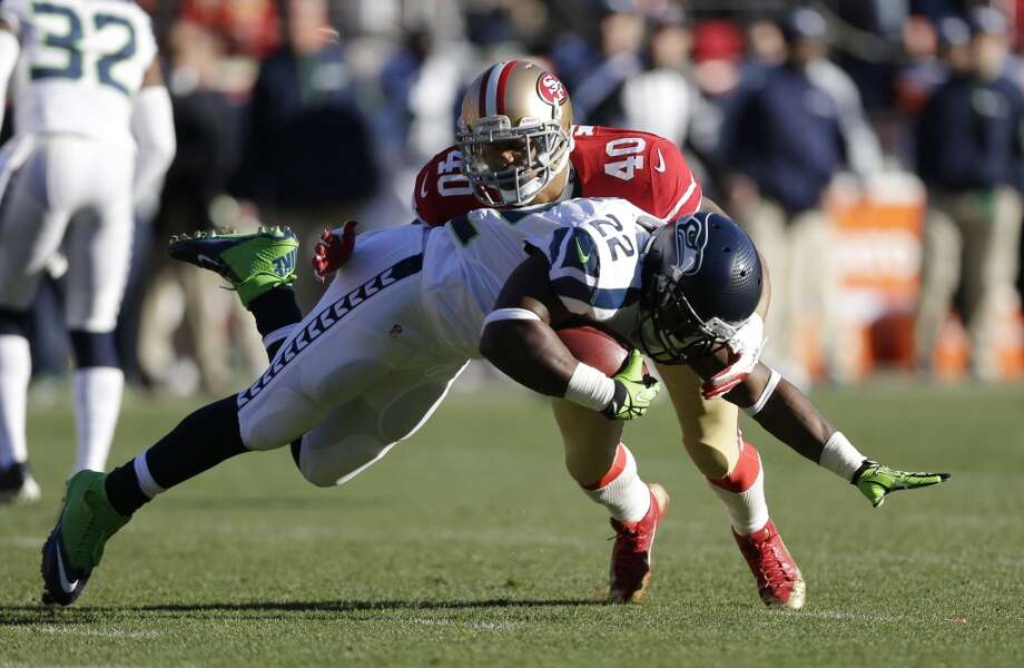 Seattle Seahawks running back Robert Turbin (22) is stopped with the ball by San Francisco 49ers defensive back Darryl Morris (40) in the first half of an NFL football game, Sunday, Dec. 8, 2013, in San Francisco. (AP Photo/Marcio Jose Sanchez) Photo: Marcio Jose Sanchez, AP