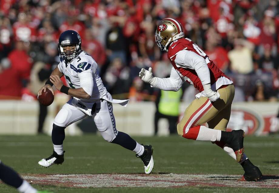 Seattle Seahawks quarterback Russell Wilson, left, runs with the ball as San Francisco 49ers outside linebacker Aldon Smith, right, looks on in the first half of an NFL football game, Sunday, Dec. 8, 2013, in San Francisco. (AP Photo/Marcio Jose Sanchez) Photo: Marcio Jose Sanchez, ASSOCIATED PRESS