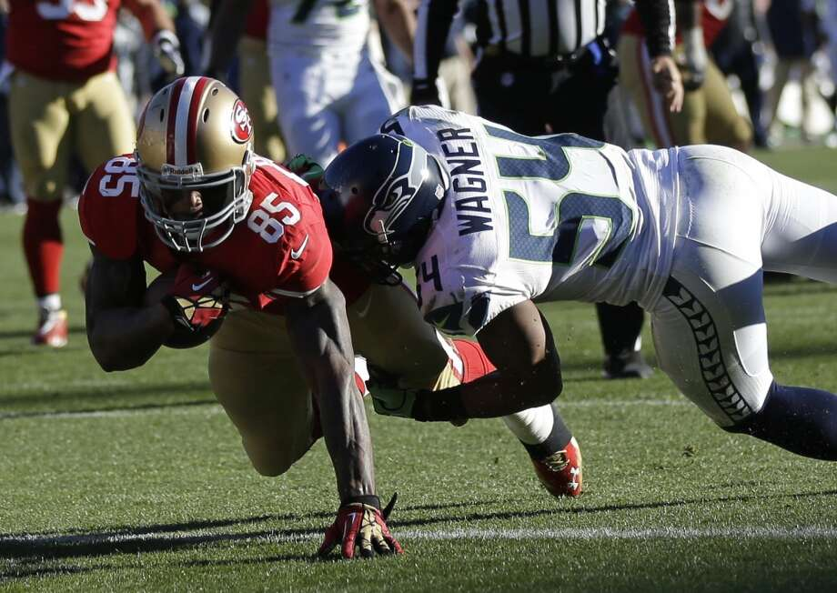 San Francisco 49ers tight end Vernon Davis, left, carries the ball over the goal line for a touchdown after a pass reception as Seattle Seahawks middle linebacker Bobby Wagner, right, defends in the first half of an NFL football game, Sunday, Dec. 8, 2013, in San Francisco. (AP Photo/Marcio Jose Sanchez) Photo: Marcio Jose Sanchez, AP