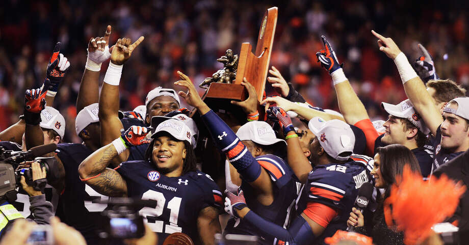 Auburn running back and SEC MVP Tre Mason (21) celebrates with teammates as they hoist the SEC Championship Trophy following the victory over Missouri in the SEC Championship Game at Georgia Dome in Atlanta, Ga. on Saturday Dec. 7, 2013. (AP Photo/Mickey Welsh, Montgomery Advertiser) ORG XMIT: ALMON101 Photo: Mickey Welsh / MONTGOMERY ADVERTISER