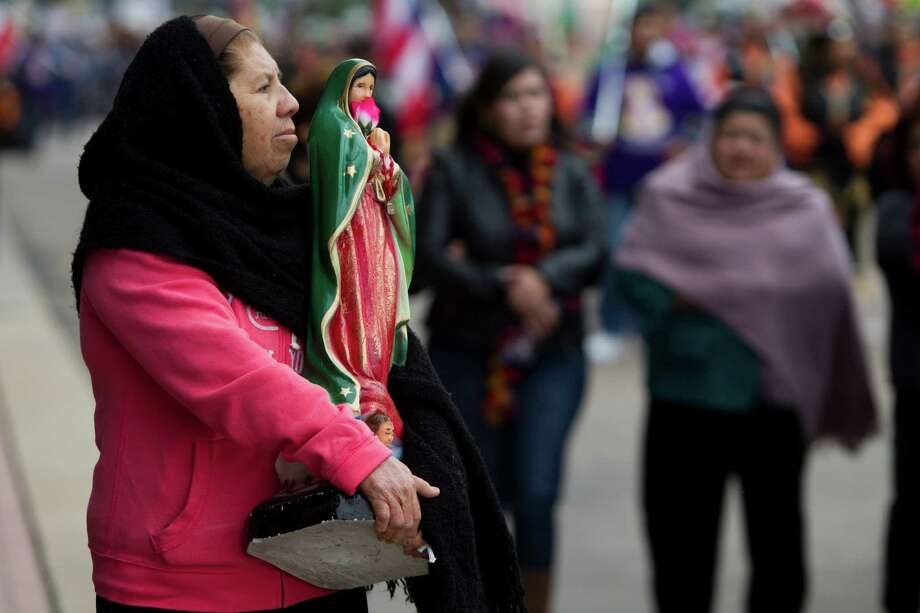 Graciela Ramirez walks the Feast of Our Lady of Guadalupe procession holding the Virgin of Guadalupe  statue during a cold afternoon near the  George B. Brown Convention Center. Photo: Marie D. De Jesus, Houston Chronicle / © 2013 Houston Chronicle