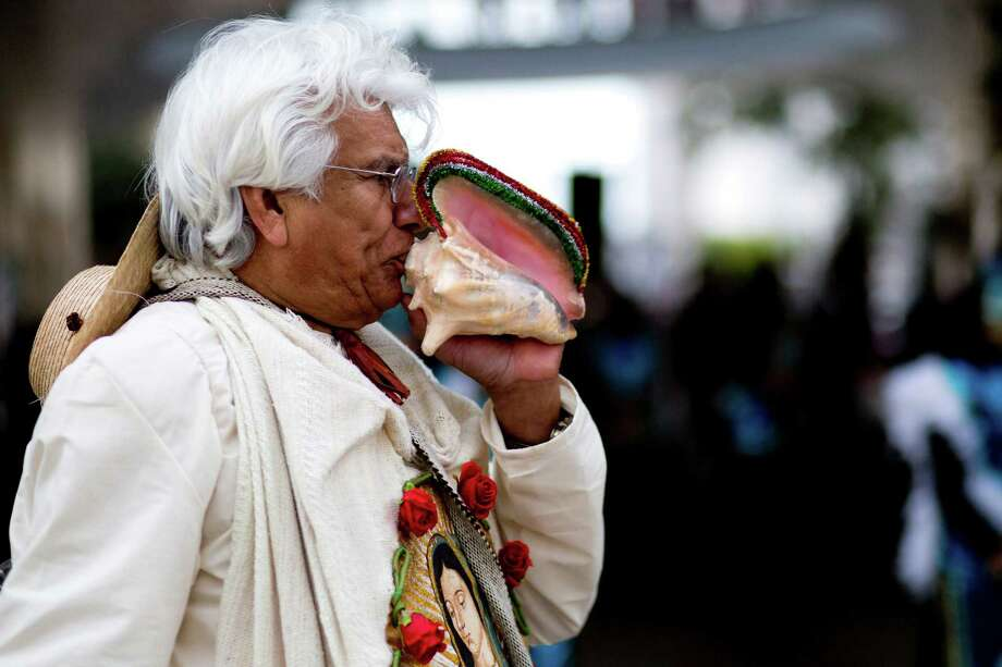 Pablo Muñoz serves as a quiquizoani or a Aztec conch trumpeter during the Feast of Our Lady of Guadalupe procession.  The sounds of conch shells and prayers initiate the procession to the George R. Brown Convention Center where the devotees will take mass. Photo: Marie D. De Jesus, Houston Chronicle / © 2013 Houston Chronicle