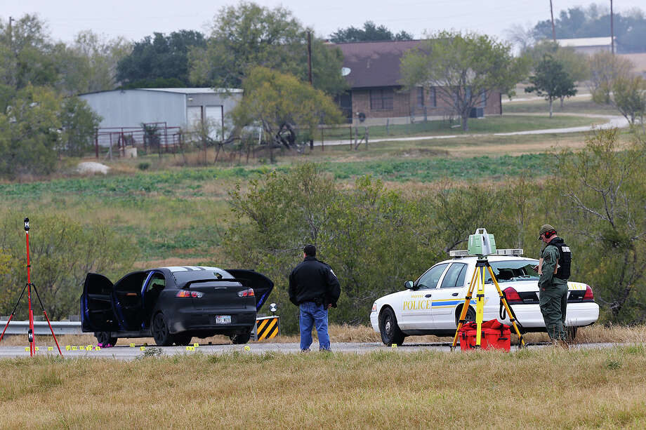 Officers investigate the scene of the shooting of a San Antonio police officer during a chase with armed robbery suspects Sunday along U.S. 181 near Floresville. Photo: Jerry Lara, Staff / ©2013 San Antonio Express-News