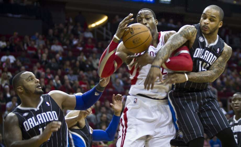 Rockets center Dwight Howard tries to keep possession between two Orlando defenders. Photo: Marie D. De Jesus, Houston Chronicle