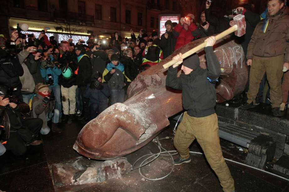 An anti-government protester beats the statue of Vladimir Lenin with a sledgehammer in Kiev, Ukraine, Sunday, Dec. 8, 2013. Anti-government protesters have toppled the statue of Bolshevik leader Vladimir Lenin in central Kiev amid huge protests gripping Ukraine. (AP Photo/Sergei Chuzavkov) ORG XMIT: XAZ138 Photo: Sergei Chuzavkov / AP