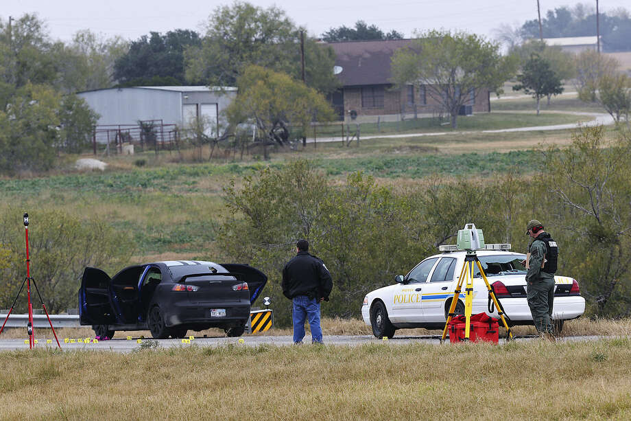 Law enforcement personnel investigate a car on U.S. 181 near Poth believed to be used in a chase in which SAPD Officer Robert Deckard was shot in the head. He had been pursuing armed-robbery suspects from San Antonio into Atascosa County.