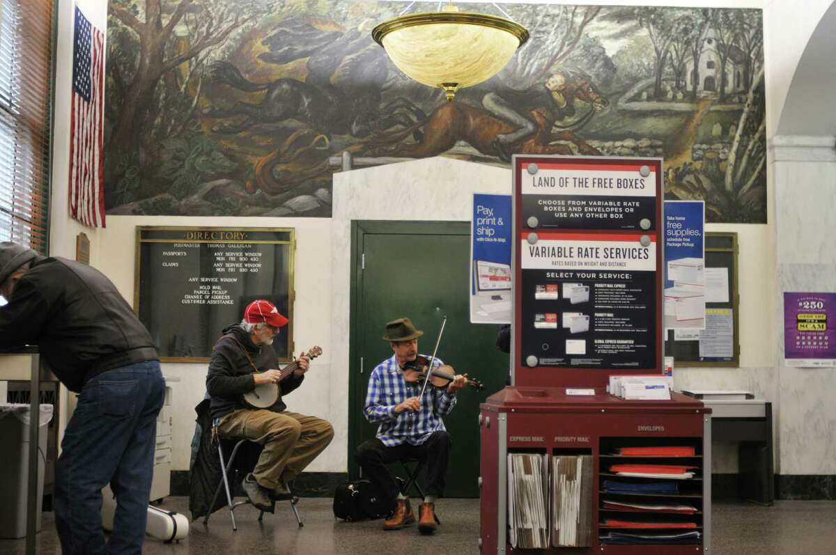 Musicians, Ron Gordon, left, of Schenectady and Ed Lowman of Greenfield Center perform in the lobby of the Post Office during the Troy Victorian Stroll on Sunday, Dec. 8, 2013 in downtown Troy, NY. (Paul Buckowski / Times Union)