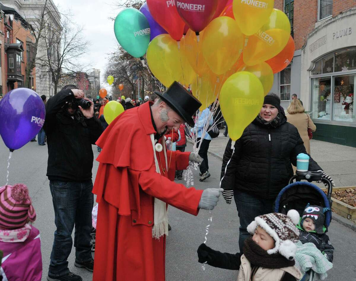Jim McGlynn, vice president of Pioneer Bank, is dressed in victorian clothing as he hands out balloons during the Troy Victorian Stroll on Sunday, Dec. 8, 2013 in downtown Troy, NY. (Paul Buckowski / Times Union)
