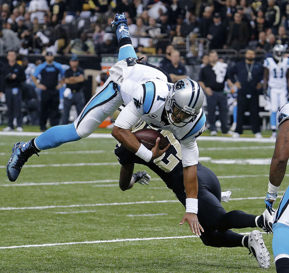 Carolina Panthers quarterback Cam Newton (1) is upended as he carries against New Orleans Saints free safety Malcolm Jenkins (27) in the first half of an NFL football game in New Orleans, Sunday, Dec. 8, 2013. (AP Photo/Bill Haber)