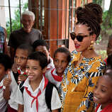 U.S. singer Beyonce poses for photos with school children as she tours Old Havana, Cuba, Thursday, April 4, 2013. Beyonce is in Havana with her husband, rapper Jay-Z, on their fifth wedding anniversary.