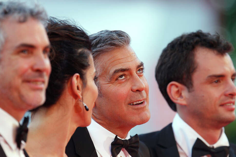 Actor George Clooney, third from left, gestures as he poses for photographers with from left director Alfonso Cuaron, actress Sandra Bullock, and screenwriter Jonas Cuaron on the red carpet for the screening of Gravity at the 70th edition of the Venice Film Festival held from Aug. 28 through Sept. 7, in Venice, Italy, Wednesday, Aug. 28, 2013. Photo: Andrew Medichini, ASSOCIATED PRESS / AP2013