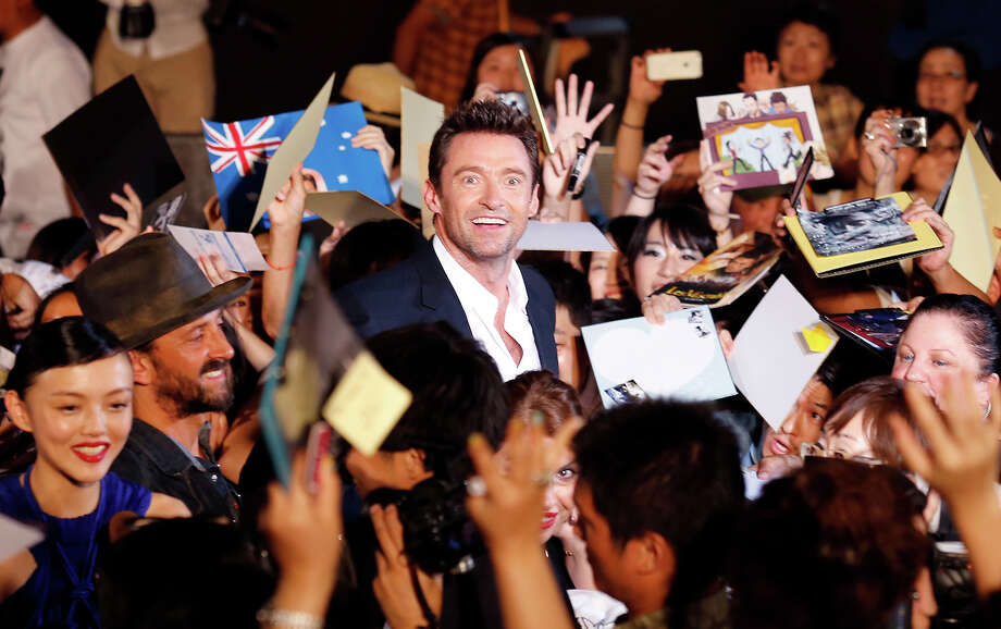 "Hugh Jackman, center, smiles as he gives his autographs to fans during the Japan premiere of his film ""The Wolverine"" in Tokyo Wednesday, Aug. 28, 2013. Smiling at bottom left is Japanese actress Rila Fukushima Photo: Shuji Kajiyama, ASSOCIATED PRESS / AP2013"