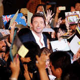 "Hugh Jackman, center, smiles as he gives his autographs to fans during the Japan premiere of his film ""The Wolverine"" in Tokyo Wednesday, Aug. 28, 2013. Smiling at bottom left is Japanese actress Rila Fukushima"