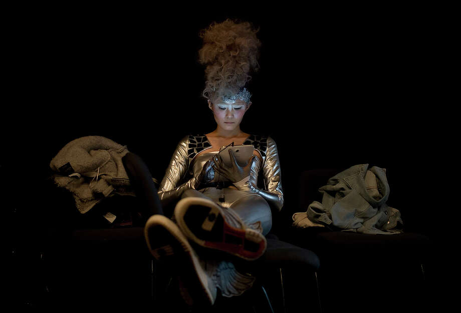A model with a hairstyle created by Chinese hairstylist Wu Jia plays a tablet computer as she prepares for the L'Oreal Hairstyling Show at China Fashion Week in Beijing Friday, Nov. 1, 2013. Photo: Andy Wong, AP / AP