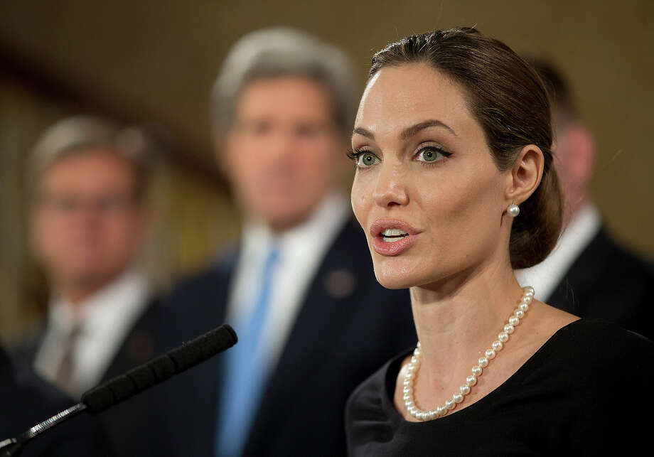 Flanked by G8 Foreign Ministers, US actress Angelina Jolie, in her role as UN envoy, talks during a news conference regarding sexual violence against women in conflict, during the G8 Foreign Ministers meeting in London, Thursday, April, 11, 2013. The ministers are meeting in London as Britain currently holds the G8 Presidency, with the heads of government G8 meeting set for June in Northern Ireland. Photo: Alastair Grant, ASSOCIATED PRESS / AP2013