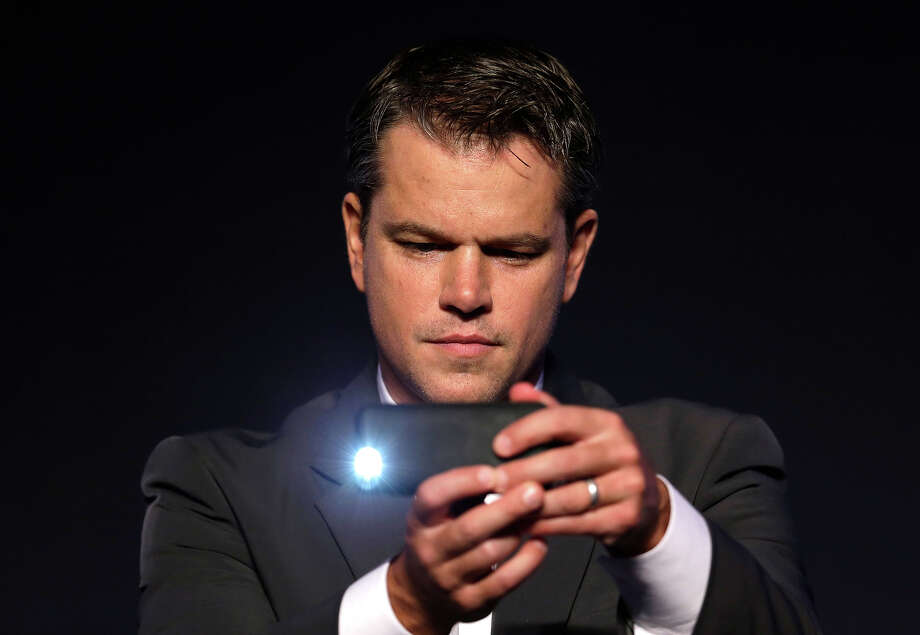 "Actor Matt Damon uses his mobile phone camera to take pictures during a press conference of his new film ""Elysium"" in Seoul, South Korea, Wednesday, Aug. 14, 2013. The film be released in South Korea on Aug. 29. Photo: Lee Jin-man, ASSOCIATED PRESS / THE ASSOCIATED PRESS2013"