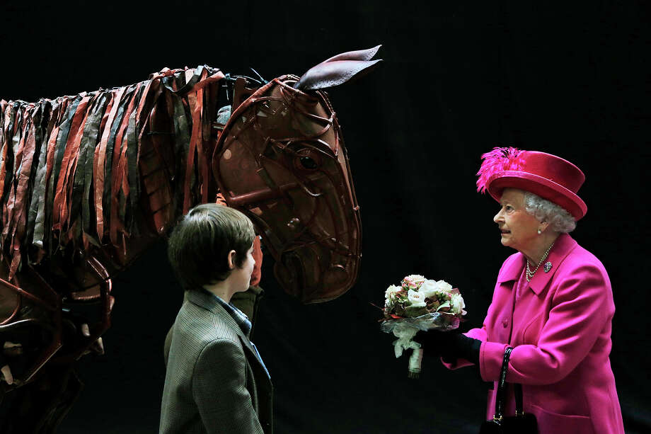 Britain's Queen Elizabeth II receives flowers from a child actor as she inspects the horse prop from the theatre production 'War Horse' during a visit at the National Theatre in London, Tuesday Oct. 22, 2013 to commemorate the institution's 50th anniversary. Photo: Lefteris Pitarakis, ASSOCIATED PRESS / AP2013