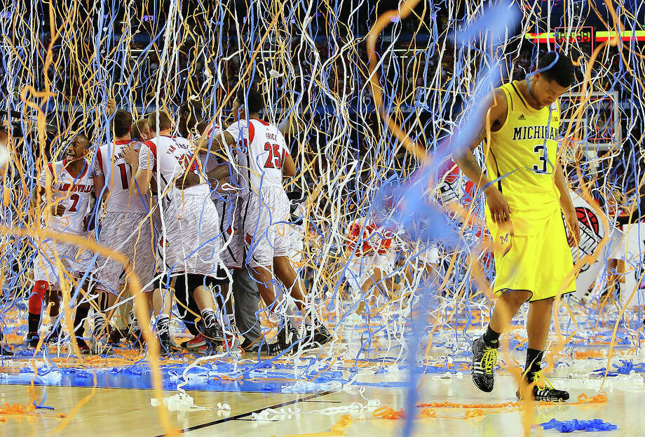 Michigan guard Trey Burke (3) walks off the court as confetti falls on Louisville players, including Russ Smith (2), Luke Hancock (11), Stephan Van Treese (44) and Zach Price (25), after the NCAA Final Four tournament college basketball championship game, Monday, April 8, 2013, in Atlanta. Louisville won 82-76. Photo: Curtis Compton, ASSOCIATED PRESS / AP2013