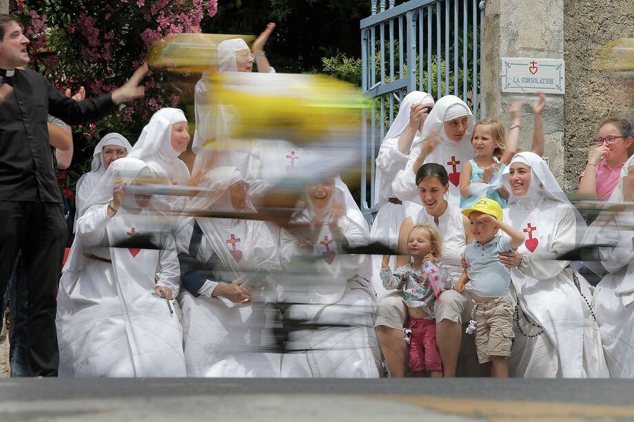 Nuns of the Monastere de la Consolation in Draguignan cheer as Simon Gerrans of Australia, wearing the overall leader's yellow jersey, passes during the fifth stage of the Tour de France cycling race over 228.5 kilometers (142.8 miles) with start in Cagnes-sur-Mer and finish in Marseille, southern France, Wednesday July 3, 2013. Photo: Laurent Cipriani, ASSOCIATED PRESS / AP2013