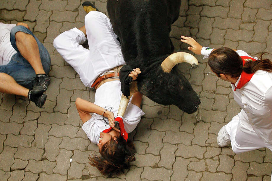 A reveler is tossed by a Dolores Aguirre Yabarra ranch fighting bull during the running of the bulls of the San Fermin festival, in Pamplona Spain, Saturday, July 7, 2012. Photo: Daniel Ochoa De Olza, ASSOCIATED PRESS / AP2012