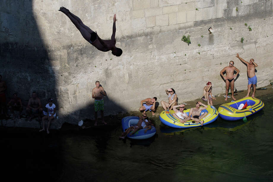 Spectators watch as a diver jumps from the Old Mostar Bridge during 447th traditional annual high diving competition, in Mostar, 140 kms south of Bosnian capital of Sarajevo, Sunday, July 28, 2013. Total of 53 divers from Bosnia and neighboring countries competed diving 25 meters high Old Mostar Bridge into the Neretva river. Photo: Amel Emric, ASSOCIATED PRESS / AP2013