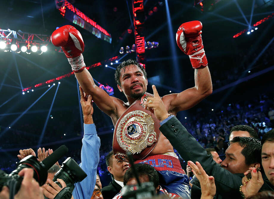 Manny Pacquiao from the Philippines wears the champion's belt after defeating Brandon Rios of the United States in their WBO international welterweight title fight Sunday, Nov. 24, 2013, in Macau. Pacquiao defeated Rios by unanimous decision on Sunday to take the WBO international welterweight title and return to his accustomed winning ways after successive defeats. Photo: Vincent Yu, ASSOCIATED PRESS / AP2013