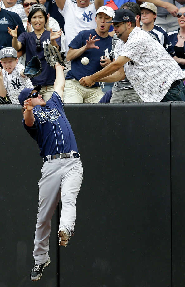 Alfonso Soriano's third-inning, two-run home run lands in the stands as Tampa Bay Rays right fielder Wil Myers leaps trying to corral it during a baseball game Sunday, July 28, 2013, in New York. Photo: Kathy Willens, ASSOCIATED PRESS / AP2013