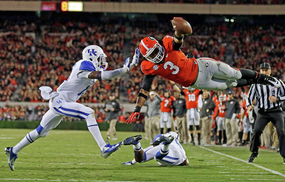 Georgia running back Todd Gurley (3) dives into the end zone for a touchdown as Kentucky cornerback Jaleel Hytchye, left, defends in the first half of an NCAA college football game on Saturday, Nov. 23, 2013, in Athens, Ga. Photo: John Bazemore, ASSOCIATED PRESS / AP2013