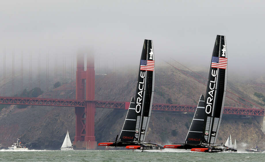 A pair of Oracle Team USA catamarans race each other past the Golden Gate Bridge enshrouded in the fog while training for the America's Cup sailing event on Saturday, Aug. 24, 2013, in San Francisco. Photo: Eric Risberg, ASSOCIATED PRESS / AP2013